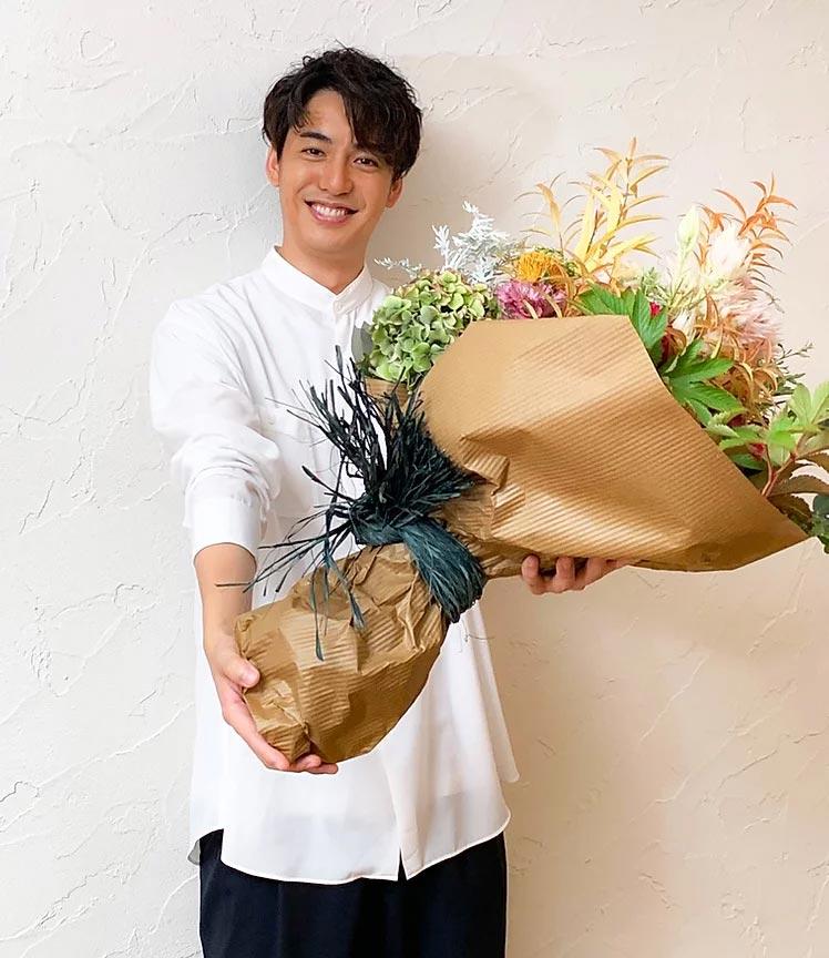 大野拓朗さんが花束を持っている